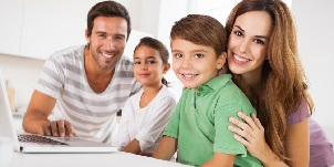 Happy family looking at the camera with a laptop in kitchen2.jpg